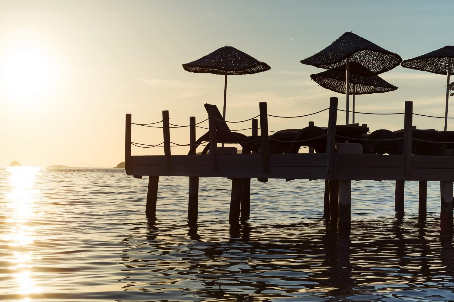 Dawn of the sun rising from the horizon of the sea. Pontoon moored on the seashore with sunbeds and umbrellas